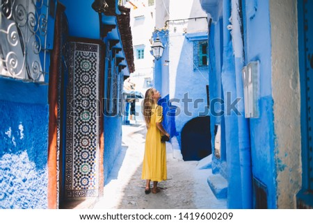 Beautiful girl with amateur camera standing in tourists city - Morocco inspecting oriental mosaic and blue walls, back view of Caucasian woman walking between ancient houses in old arabic medina