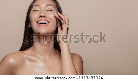 Photo of  Beautiful girl with bare shoulders applying cream on her face and smiling against beige background. Smiling asian woman with glowing skin applying facial skincare cream with eyes closed.