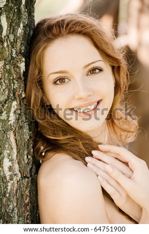 Beautiful girl with bared shoulders leans against tree in city park.