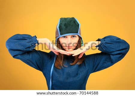 Beautiful girl  with big, blue eyes in strange clothes on orange background