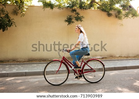 Beautiful girl with blond hair happily riding bicycle. Portrait of young lady in jeans and sunglasses on head having fun while riding on red bicycle along city streets