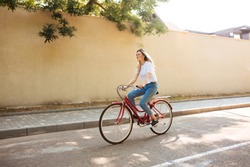 Beautiful girl with blond hair happily riding bicycle. Portrait of young lady in jeans having fun while riding on red bicycle along city streets