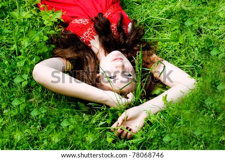 Beautiful girl with blue eyes lying on green grass