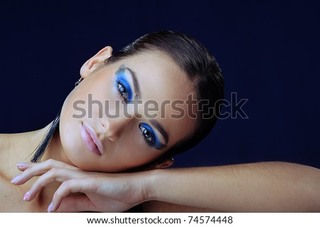 beautiful girl with blue make-up in long earrings