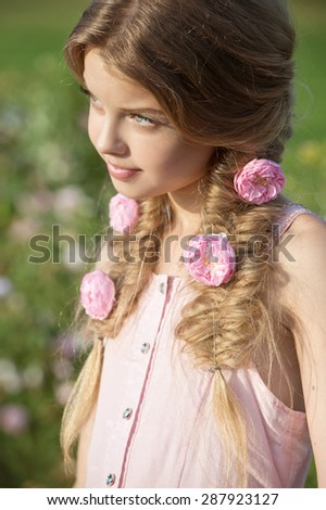 Beautiful girl with braids in garden of roses