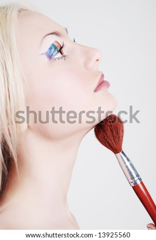 Beautiful girl with bright make-up, looks through a shoulder and holds a brush in a hand