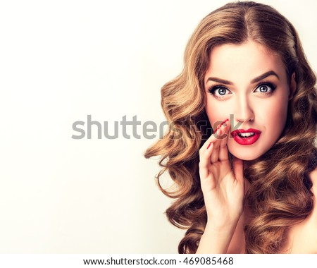 Beautiful girl with bright makeup and curly hair   telling a secret .Portrait  young happy woman who is calling to someone .Funny girl model  whispering about something. Expressive facial expressions #469085468