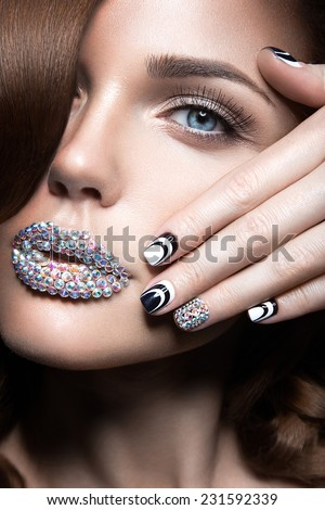 Beautiful girl with bright nails and lips of crystals, long eyelashes and curls. Beauty face. Picture taken in a studio.