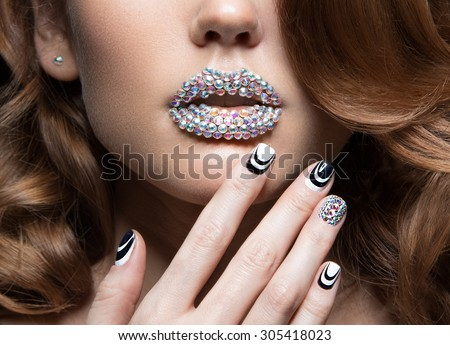 Beautiful girl with bright nails, lips of crystals, long eyelashes and curls. Beauty face.