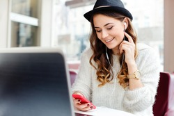 Beautiful girl with brown curly hair and dark manicure wearing white sweater, black hat and watch sitting in cafe with laptop, mobile phone and headphones.