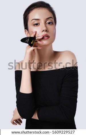 Beautiful girl with butterflies in studio.Nude makeup.Fashion portrait