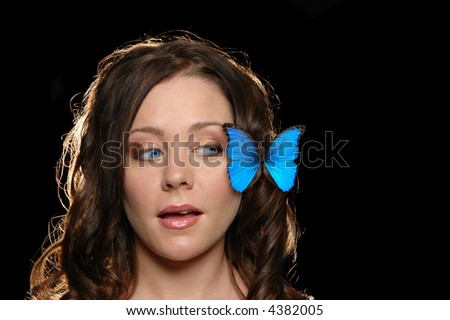 Beautiful girl with butterfly on her face against a black black ground