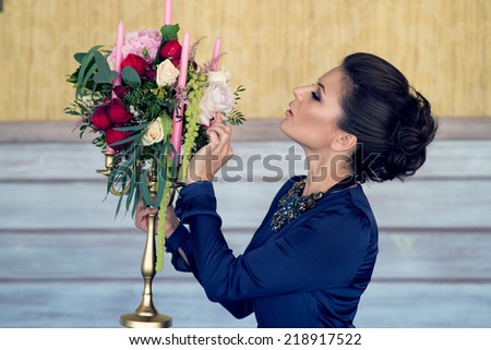 Beautiful girl with candelabra decorated with flowers #218917522