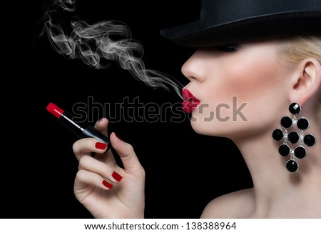 Beautiful girl with cigarette and red lips on black background