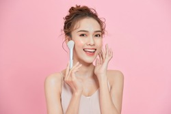 Beautiful girl with cosmetic powder brush for make up. Makeup