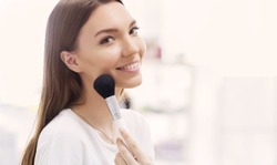 Beautiful girl with cosmetic powder brush for make up. Makeup. Make-up applying  for perfect skin.