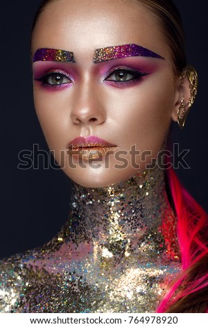 Beautiful girl with creative glitter makeup with sparkles, unusual eyebrows. Beauty is an art face. Photo taken in the studio.