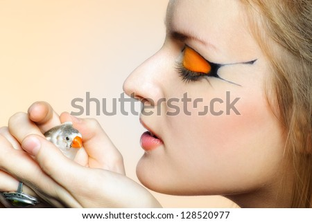 Beautiful girl with creative makeup and bird in her hands