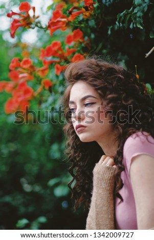 Beautiful girl with curls and freckles. Bright flowers on the background. Fashion, style, beauty. Beauty template