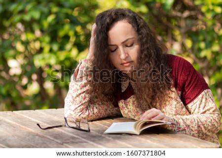Beautiful girl with curly hair listens to music. Sometimes he reads books.