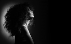 beautiful girl with curly hair on a black background looking to the side, her eyes closed, black and white photo