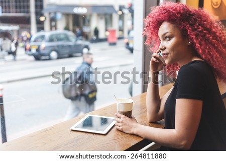 Beautiful girl with curly red hair talking on smart phone in a cafe. Also she is holding a cup of coffee and she has a digital tablet on the table.