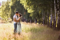 Beautiful girl with dark hair and brown eyes with a wreath on head in summer dress hugging a man in awhite shirt on a green background. Loving couple in the forest on a sunny day. To love each other