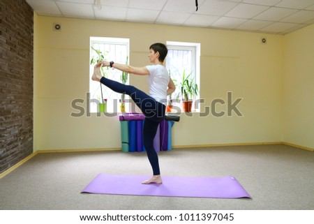 Stock Photo Beautiful girl with dark hair engaged in fitness studio, woman sitting on cross twine and doing stretching exercises. Room is light and bright, high walls painted in yellow color, in room large