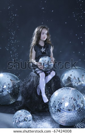 Beautiful girl with disco balls. Black background