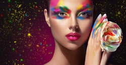 Beautiful girl with festive bright multi-colored make up  on the face. Young woman dressed in extravagant art makeup .Twinkling stars on a black background. Holiday ,celebration, cosmetic and beauty .