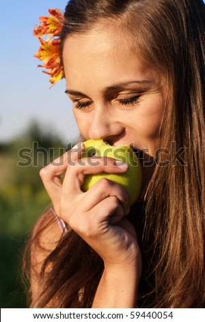 Beautiful girl with flower in hair bite apple outdoors