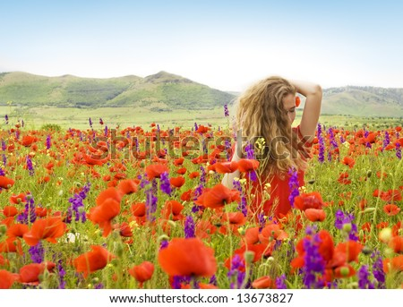 beautiful girl with flowers in her hair in a field with poppies and violet flowers