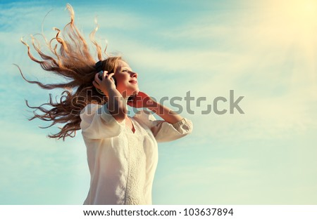 beautiful girl with flying  blond hair, listening to music on headphones in the sky