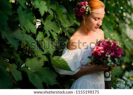 beautiful girl with fresh flowers, under the sun, against the hedge of leaves, in the afternoon #1155198175