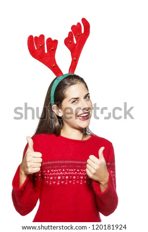 Beautiful girl with funny Christmas reindeer horns, smiling and showing thumbs up gesture. On white background