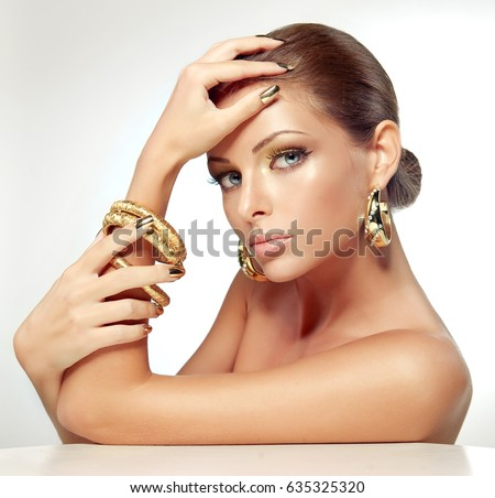 Beautiful girl with golden makeup and gold  metal manicure  nails.  Fashion woman Portrait . Jewelry and accessories