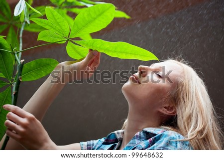 Beautiful girl with green leave under the rain - stock photo