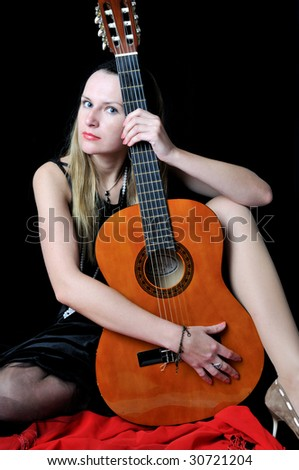 Beautiful girl with guitar, on black background