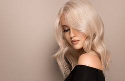Beautiful girl with hair coloring in ultra blond. Stylish hairstyle curls done in a beauty salon. Fashion, cosmetics and makeup