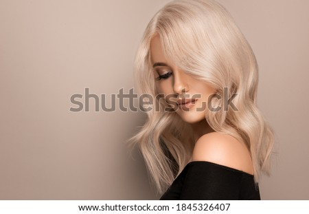 Beautiful girl with hair coloring in ultra blond. Stylish hairstyle curls done in a beauty salon. Fashion, cosmetics and makeup Stock photo ©