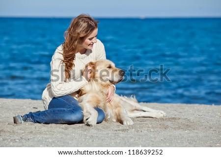 Beautiful girl with her dog  near sea