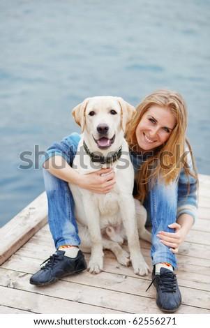 Beautiful girl with her dog on berth near sea