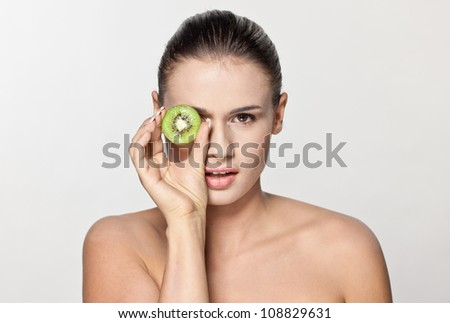 Beautiful girl with kiwi fruit at the face