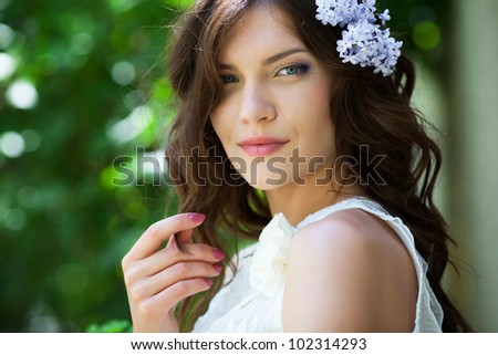 Beautiful girl with lilac flower in hair