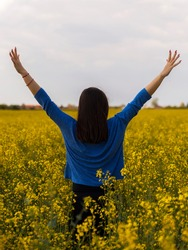Beautiful girl with long dark hair enjoying the sunlight in a field of yellow flowers,rapeseed.With back turned towards  the camera with her hands raised in the air. Celebrating life