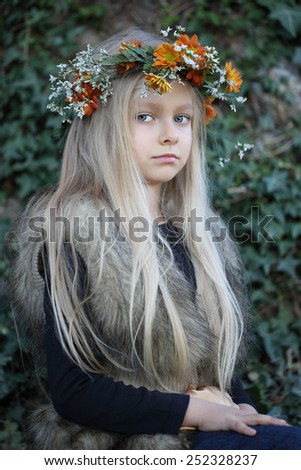 Beautiful girl with long hair and floral wreath. The child in the spring garden.