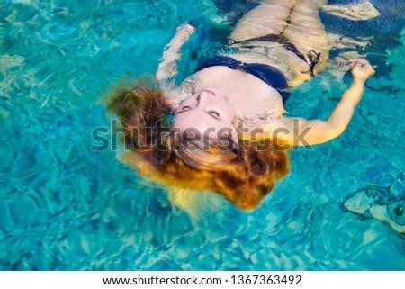 Beautiful girl with long hair enjoying in the swimming pool in spa or sauna #1367363492