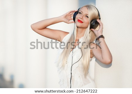 beautiful girl with long hair enjoys music with headphones in the sky with your eyes closed. Beautiful young woman with headphones. Enjoy music outdoors.