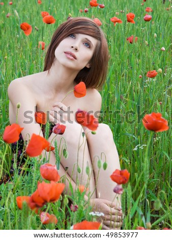 beautiful girl with long hair posing at poppy meadow