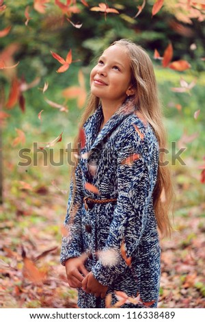 Beautiful girl with long hair standing in the autumn park and looking at yellow leaves.